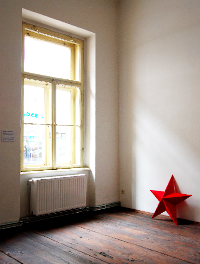 Wooden star, red paint, dusty wall.